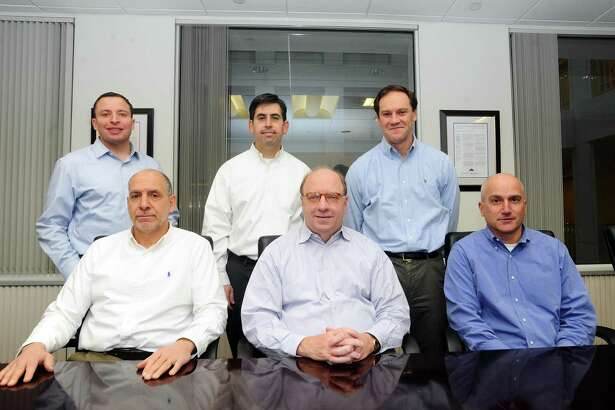 Several of private equity firm Olympus Partners' partners gather in the firm's Station Place offices in Stamford, Conn., on Dec. 19, 2017. From left, are: partner Jason Miller, managing partner Lou Mischianti, partner Evan Eason, founder and managing partner Rob Morris, partner David Haddad and partner Paul Rubin.