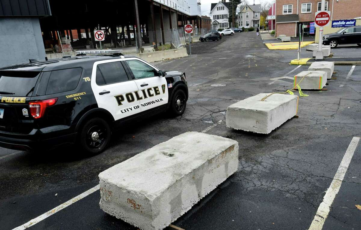 Concrete barriers block access to the parking lot Developer Jason Milligan owns on Isaac St. Tuesday, November 12, 2019, blocking the ability for cars to drive through the lot from Wall St to Leonard St. in Norwalk, Conn. Instead, drivers coming down Isaacs, will be forced to turn around and exit back to Wall St going the wrong way down a previously posted one-way street.