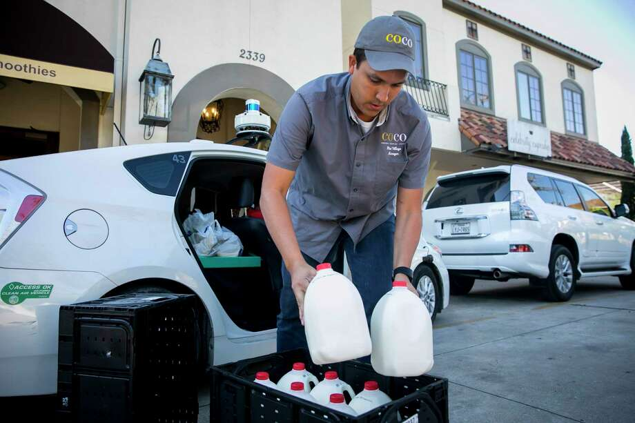 Rafael Moreno unloads milk delivered by Nuro for his Houston cafe, CoCo Crepes, Waffles and Coffee. Photo: Photo For The Washington Post By Annie Mulligan. / Annie Mulligan
