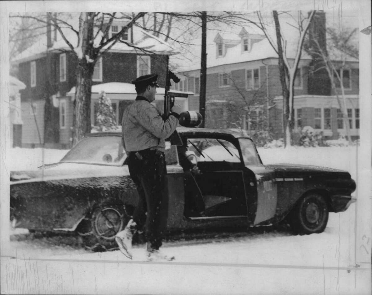 At the Thomas McAvoy shooting on Manning Boulevard, a police officer stands with a Thomson gun, Albany, New York. January 28, 1964 (Times Union Archive)