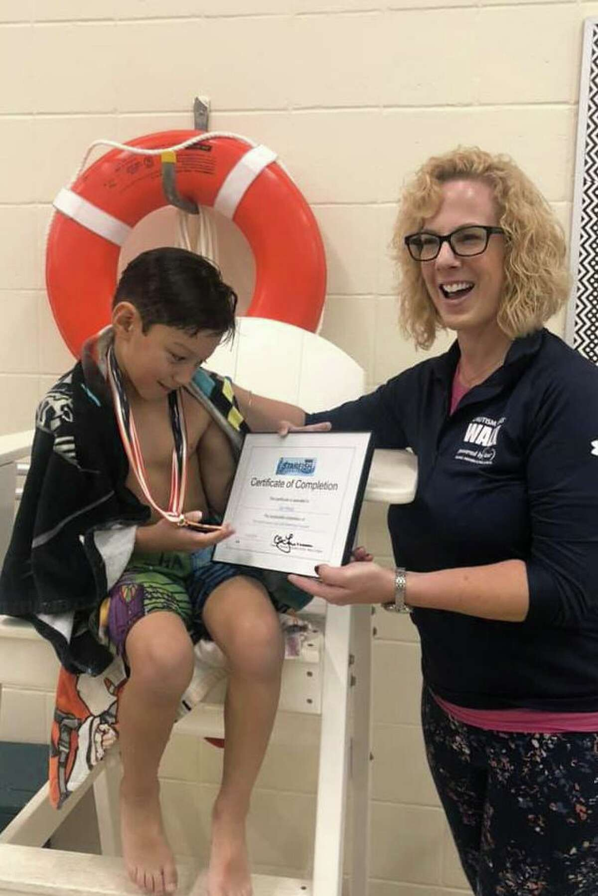Ian Perez, pictured with Christine Faressa, just graduated from a swimming program for children on the autism spectrum.