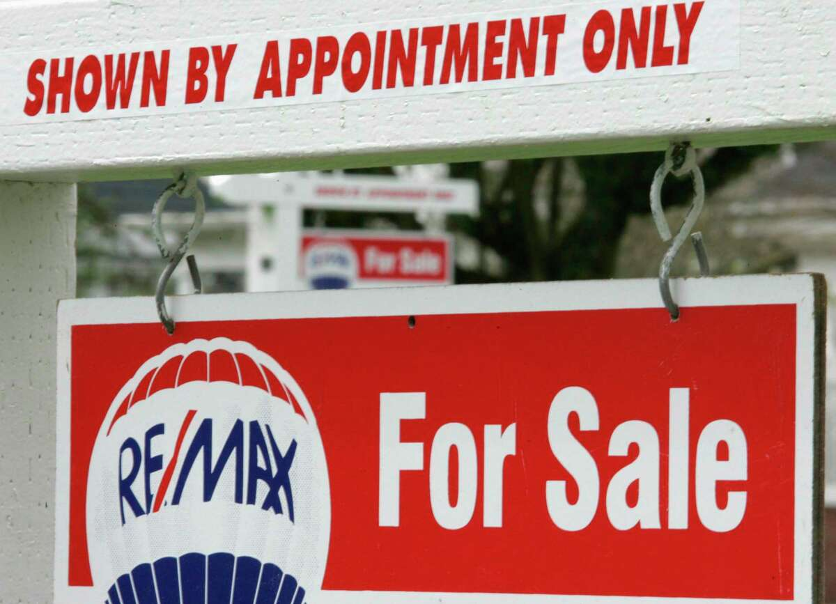 """A realtor's """"For Sale"""" sign is displayed at a home."""