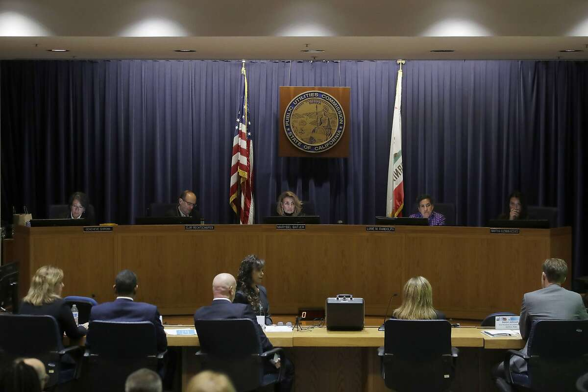 California Public Utilities Commission President Marybel Batjer, center rear, and commissioners listen as representatives of Pacific Gas and Electric Company (PG&E), seated at bottom, speak during a meeting at CPUC headquarters in San Francisco, Friday, Oct. 18, 2019. (AP Photo/Jeff Chiu)