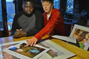 Ronnie Sseruyange, left, and Diane Reiner look over photographs in her Colonie home. Reiner met Sseruyange in 2006 when he was homeless, living on the streets of Kampala, Uganda. (John Carl D'Annibale / Times Union archive)