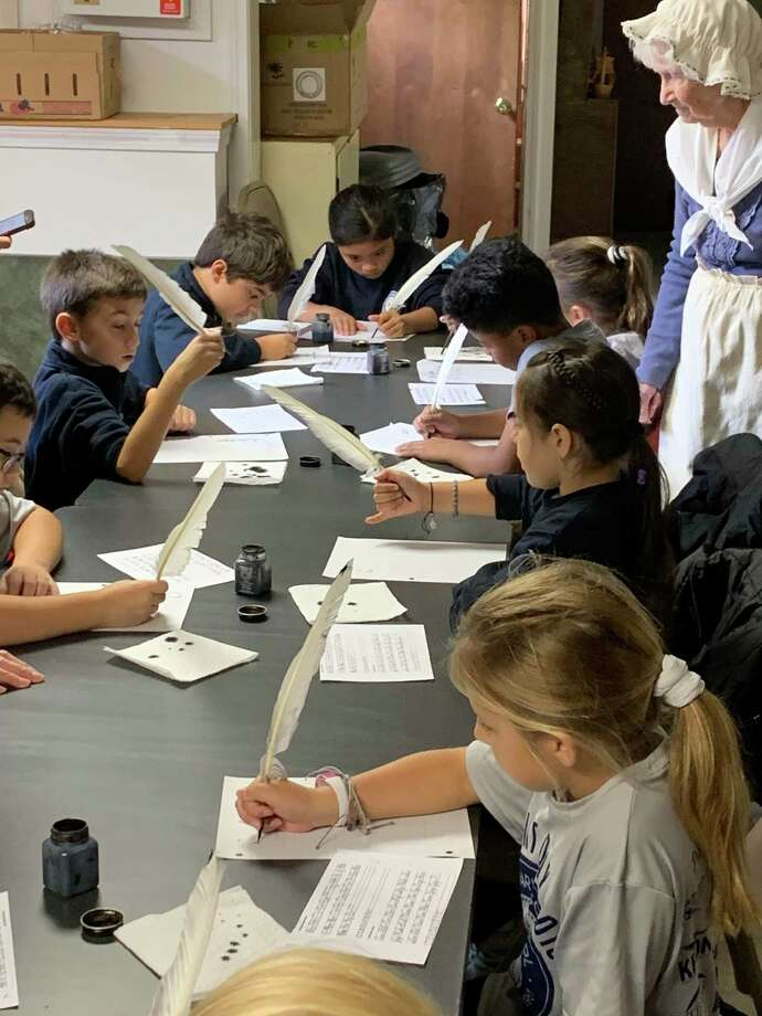 St. Mary School's third grade students recently took a field trip to the Milford Historical Society where they played with old fashioned toys, learned about life in Milford during the colonial times, wrote with quill pens and enjoyed lunch on the lawn. Photo: Contributed Photo.