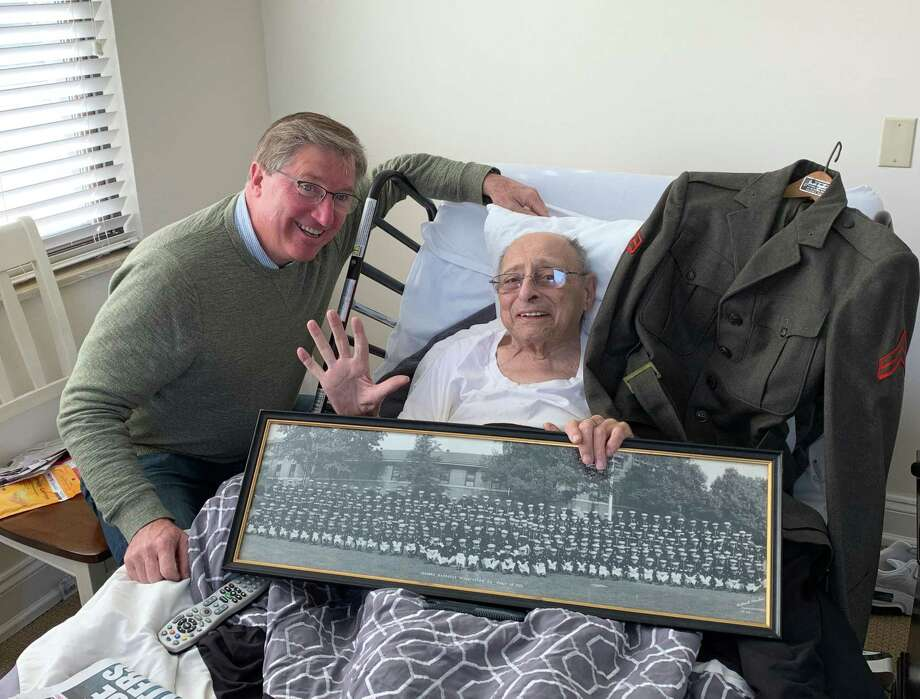 Wilton Hospice volunteer Steve Sweeney visits Stanley Epstein at his home in Stamford where he is holding a picture of his U.S. Marine Corps. platoon from his service in the Korean War. Photo: Contributed Photo / / Wilton Bulletin Contributed