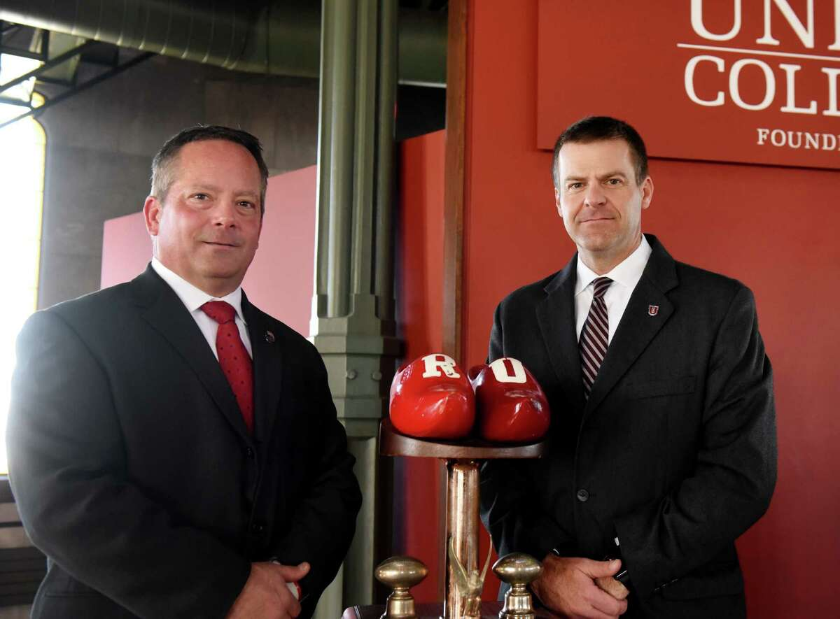 Rensselaer Polytechnic Institute football head coach, Ralph Isernia, left, and Union College football head coach, Jeff Behrman, right, stand next to the Dutchman Shoes trophy during a press conference promoting Saturday's game on Wednesday, Nov. 13, 2019, at Union College in Schenectady, N.Y. (Will Waldron/Times Union)