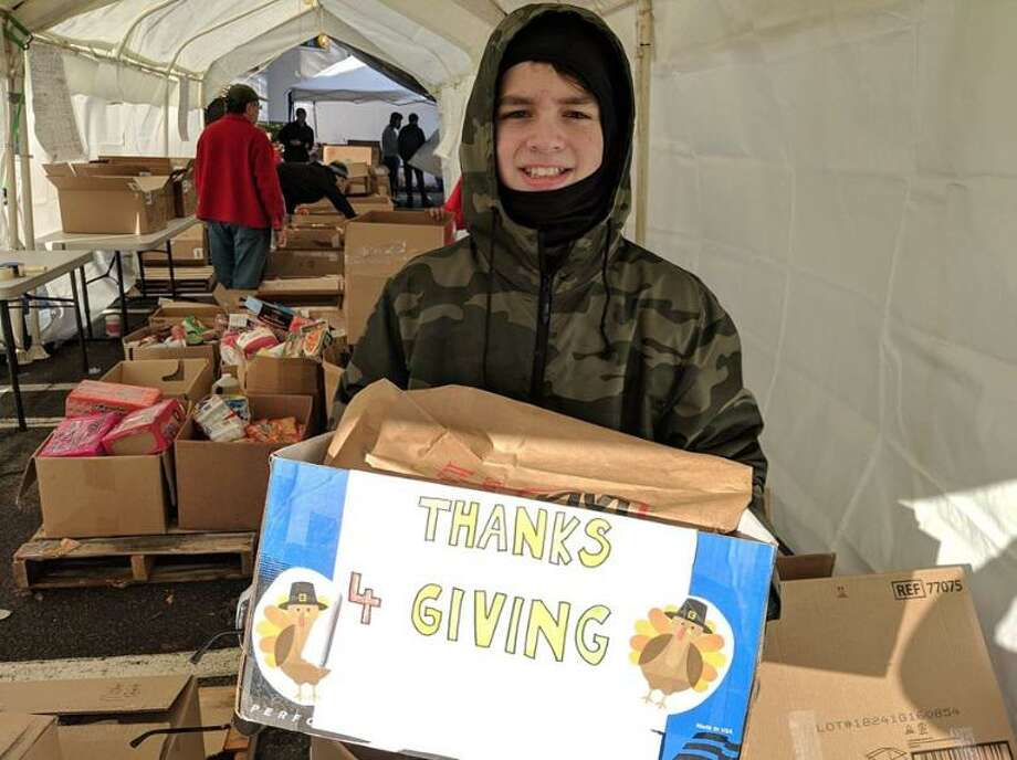 Milford Boy Scout Troop 1 member, Liam Dickman, helps sort donations during last year's ThanksforGiving Food drive. Photo: Contributed Photo.