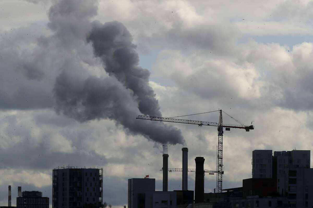 Smoke billows from a plant just outside the French capital, Wednesday, Nov. 13, 2019 in Paris. The world's thirst for oil will continue to grow until the 2030s, with climate-damaging emissions climbing until at least 2040 - and consumers' insatiable appetite for SUVs is a big reason why. (AP Photo/Michel Euler)