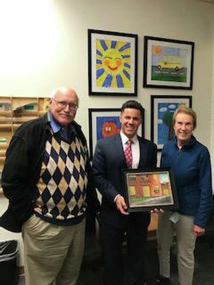 """From left, EHACC member Mel Carnahan; Center School Principal Christopher Sullivan and East Hmpton Arts & Culture Commission member Phyllis Martin show the donated painting, """"Free Love"""" by Moodus artist Skye Garofalo. Photo: Melissa Pionzio / Contributed Photo"""