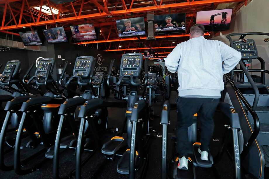 A patron concentrates on his workout on an elliptical machine while various television screens show different networks views of the Trump impeachment hearings as well as programing on HGTV and ESPN, Wednesday, Nov. 13, 2019 at Fondren Fitness. (AP Photo/Rogelio V. Solis) Photo: Rogelio V. Solis / Associated Press / Copyright 2019 The Associated Press. All rights reserved