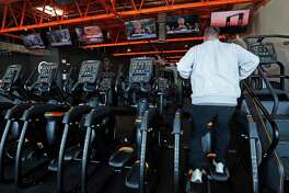 A patron concentrates on his workout on an elliptical machine while various television screens show different networks views of the Trump impeachment hearings as well as programing on HGTV and ESPN, Wednesday, Nov. 13, 2019 at Fondren Fitness. (AP Photo/Rogelio V. Solis)