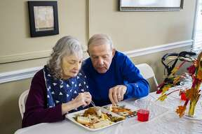 Jerry Pergande, right, helps to cut up pieces of food for his wife Joan, left, during a Harvest Dinner held at Nottingham Place assisted living facility Wednesday, Nov. 13, 2019 in Midland. (Katy Kildee/kkildee@mdn.net)