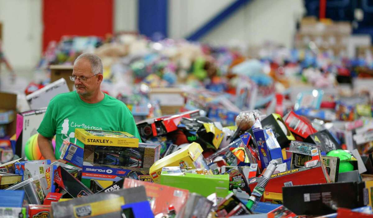 Volunteer Greg Pitcock helps sort toys behind the scene during the Houston Children's Charity Christmas Program Thursday, Dec. 21, 2017, in Houston. The program allows parents of underprivileged children the opportunity to holiday