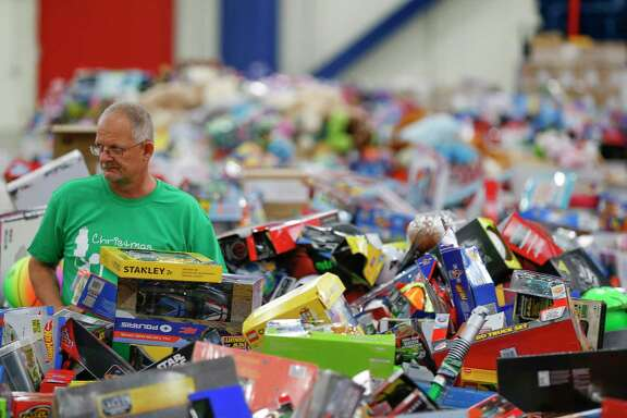 """Volunteer Greg Pitcock helps sort toys behind the scene during the Houston Children's Charity Christmas Program Thursday, Dec. 21, 2017, in Houston. The program allows parents of underprivileged children the opportunity to holiday """"shop"""" for their kids. The program was also made possible with the U.S. Marine Corps Toy for Tots program and Houston First Corporation. ( Steve Gonzales / Houston Chronicle )"""