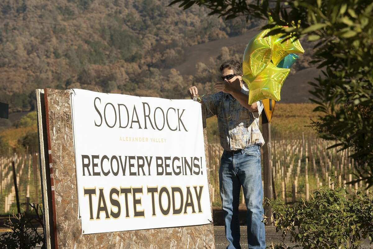 Tasting room employee Mark Dankowski tying balloons to sign letting the public know that the tasting room is up and running at Soda Rock Winery in Healdsburg, California. November 10, 2019.