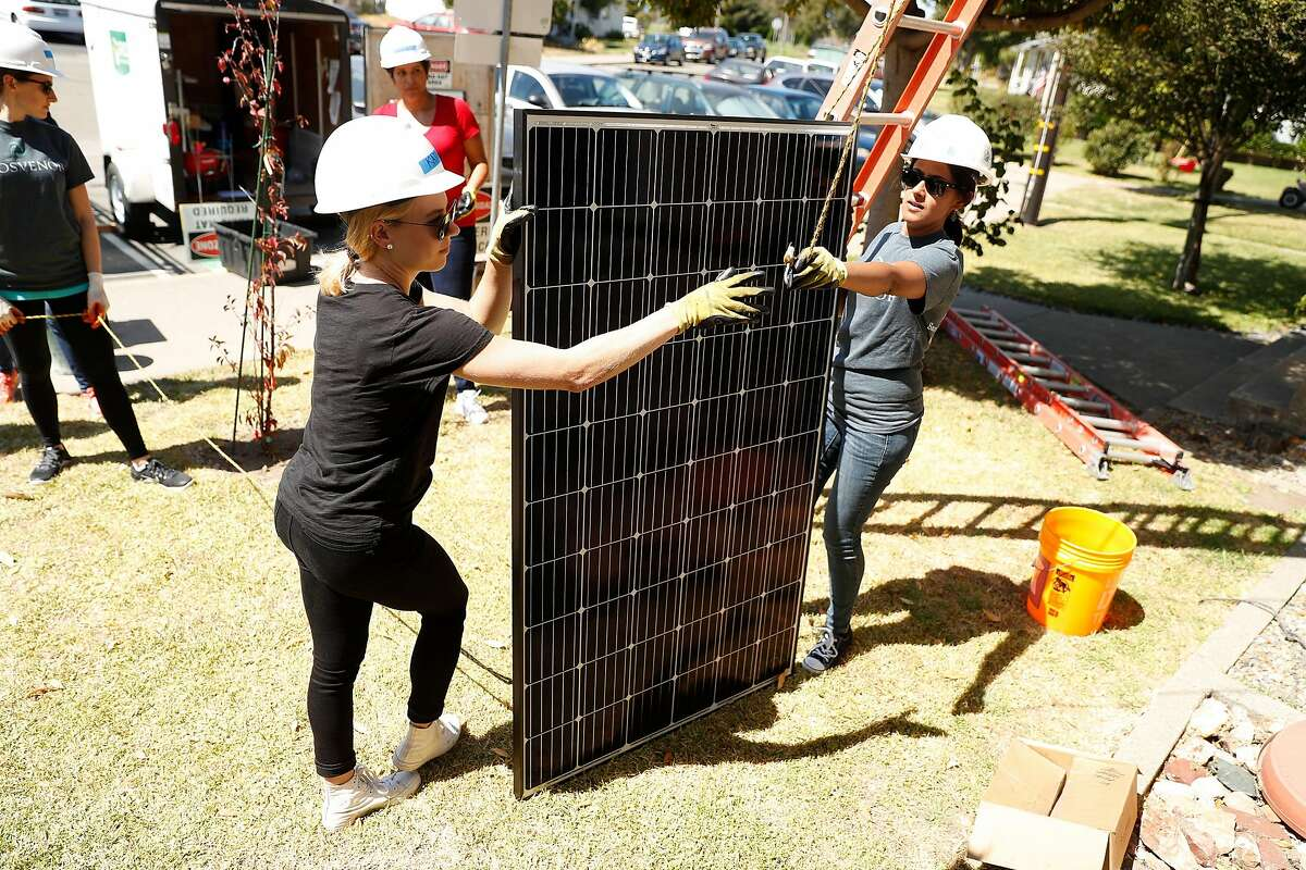 Katie Keyser and Virpal Sidhu prepare a solar panel for installation in Richmond, Calif., on Wednesday, September 11, 2019, as part of a non-profit venture to provide solar power to residential homes.