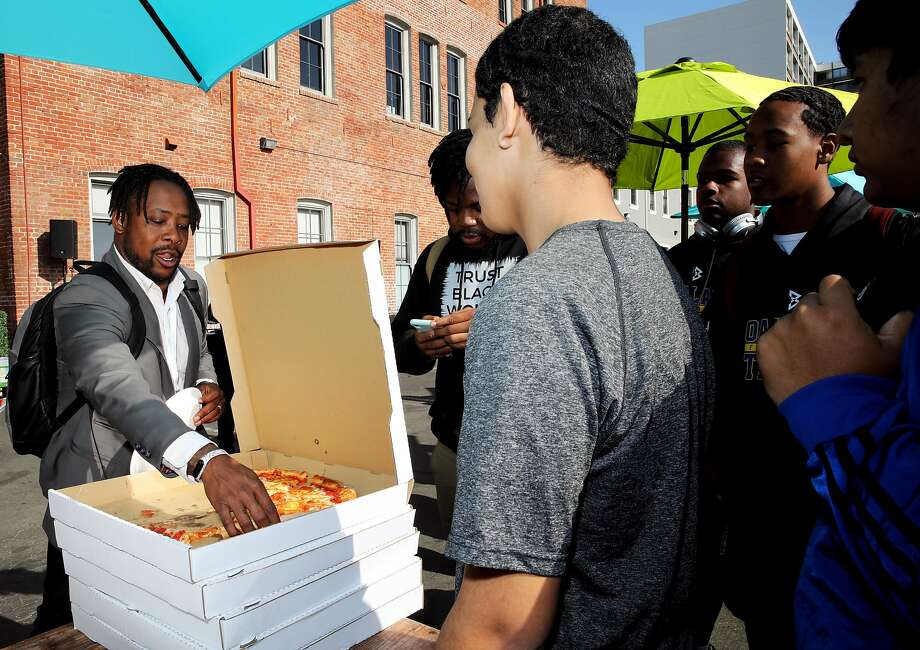 Kennan Scott (left), the OUSD's computer science manager, provides pizza at lunch for students attending the AfroTech conference Friday in downtown Oakland. Photo: Yalonda M. James / The Chronicle