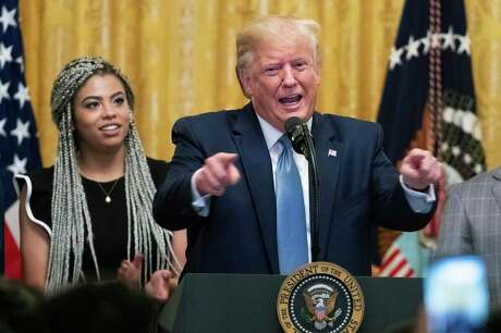 President Donald Trump speaks at the Young Black Leadership Summit 2019 in the East Room of the White House in Washington, Friday, Oct. 4, 2019. Kearyn Bolin, back left, of Texas State University listens.