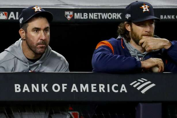 Houston Astros starting pitchers Justin Verlander (35), and Gerrit Cole (45) watch the game from the dugout during the ninth inning of Game 4 of the American League Championship Series at Yankee Stadium on Thursday, Oct. 17, 2019, in New York.