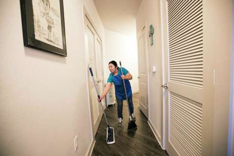 Julia De Leon, a domestic worker picks up a microfiber mop and a broom on Monday, March 4, 2019, in Houston as she starts her day cleaning up the apartment of one of her clients.