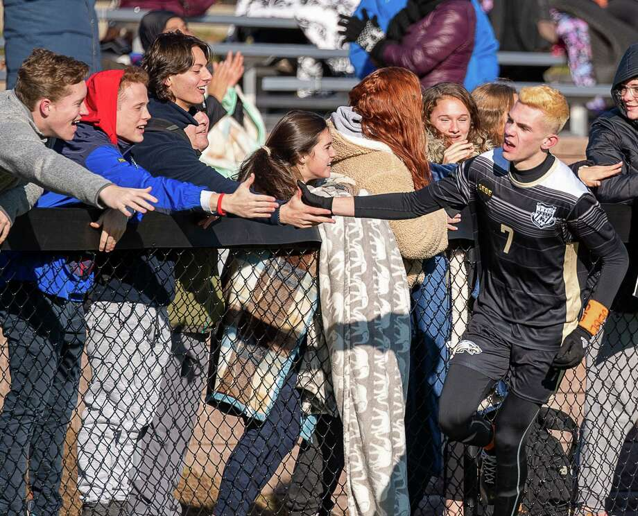 Matt Bagley gets some love from Trumbull fans after he scored his second goal in Trumbull's 6-1 victory over Shelton. Trumbull High's Matthew Bagley celebrates with the fans after his first goal against Shelton high in the second round of the CIAC CLass LL Boys Soccer State Tournament, Wednesday, November 13, 2019, at Trumbull High School. Photo: David G Whitham / For Hearst Connecticut Media / DGWPhotography