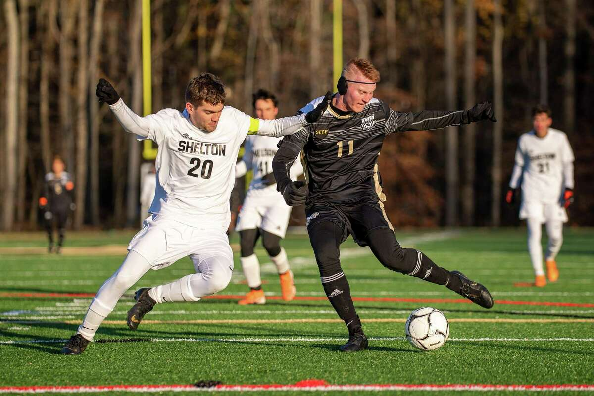 Trumbull High's Justin Horvath tries to get past Shelton's Jack Neary in the second round of the CIAC CLass LL Boys Soccer State Tournament, Wednesday, November 13, 2019, at Trumbull High School.