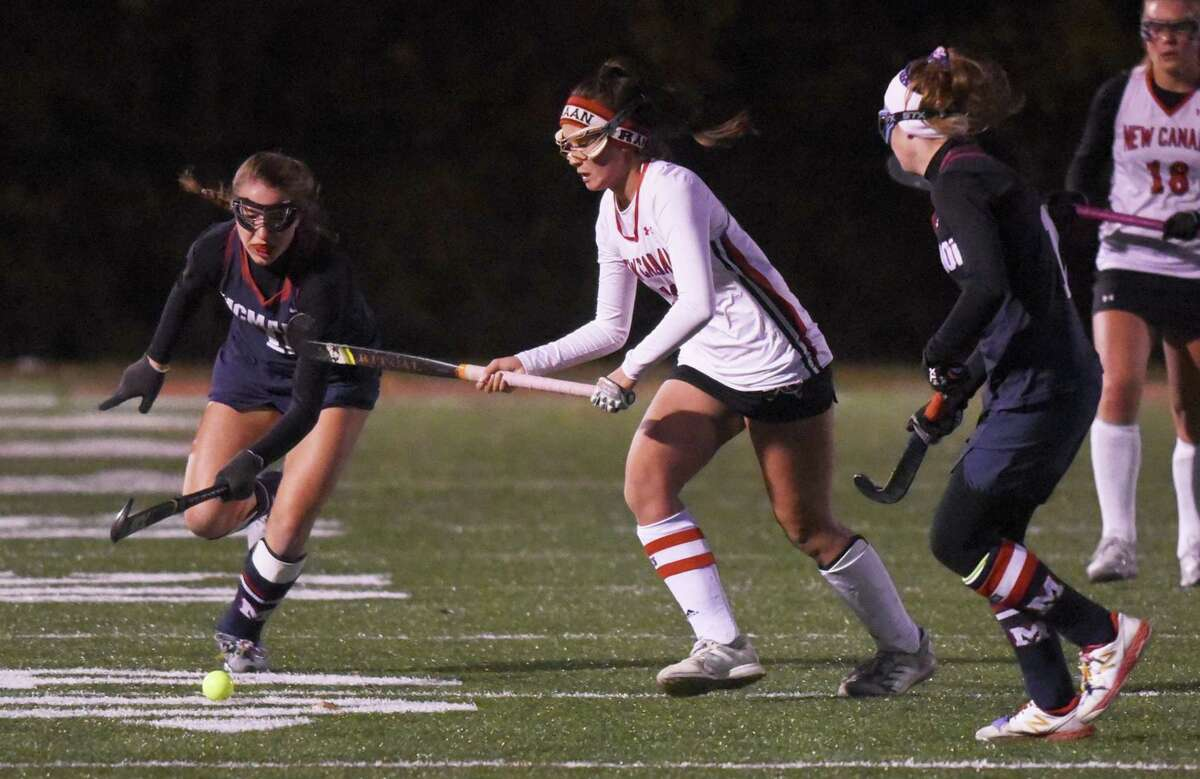 New Canaan's Estelle Asker plays the ball while Brien McMahon's Olivia Misiak (12, left) and Emma Mclaughlin (10) defend during a Class L field hockey first round game at Dunning Field on Wednesday, Nov. 13, 2019.