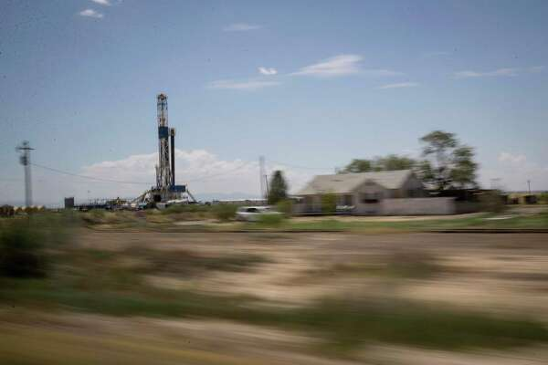 A drilling rig operates near a house near Pecos. The U.S. shale industry is shrinking to survive amid an environment of depressed crude prices and Wall Street animosity toward nearly all things oil and gas.