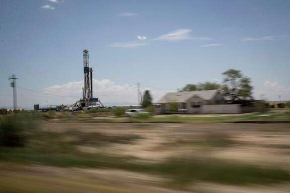 A drilling rig operates near a house on Tuesday, Aug. 20, 2019, near Pecos.