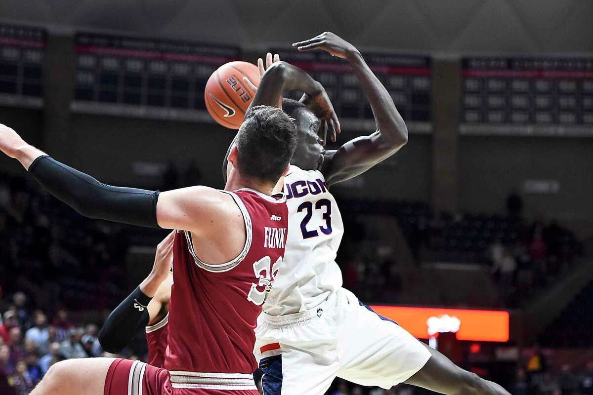 UConn's Akok Akok, right, is tangled up with Saint Joseph's Taylor Funk in the first half Wednesday in Storrs.