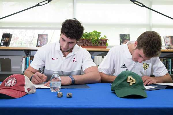 Peter Berry, left, and his cousin, Noah Berry, signing papers to play wheelchair basketball at the University of Alabama and tennis for California Polytechnic State University, respectively, at the Emery/Weiner School on Wednesday, Nov. 13, 2019, in Houston. Peter's parents were killed in a 2011 car crash and he was paralyzed. He and his two siblings were taken into Noah's family by Noah's parents.