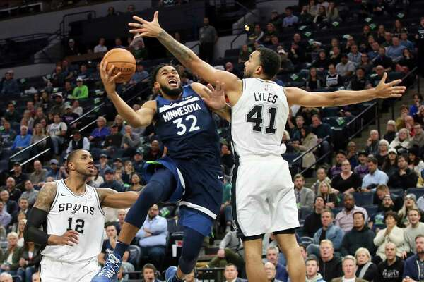 Minnesota Timberwolves' Karl-Anthony Towns , left, lays up as San Antonio Spurs' Trey Lyles defends in the second half of an NBA basketball game Wednesday, Nov 13, 2019, in Minneapolis. The Timberwolves won 129-114.