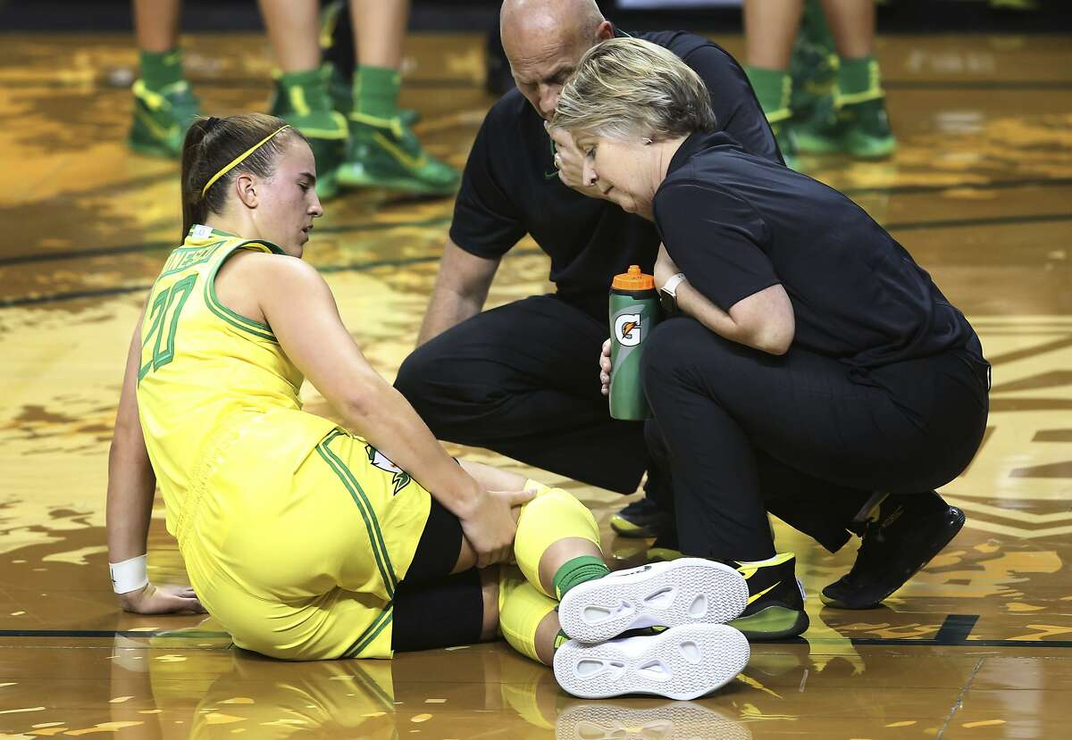 Oregon's Sabrina Ionescu, left, grabs her leg after falling to the floor as coach Kelly Graves and trainer Kim Terrell come to her aid during the second half of the team's NCAA college basketball game against Utah State in Eugene, Ore., Wednesday, Nov. 13, 2019. (AP Photo/Chris Pietsch)
