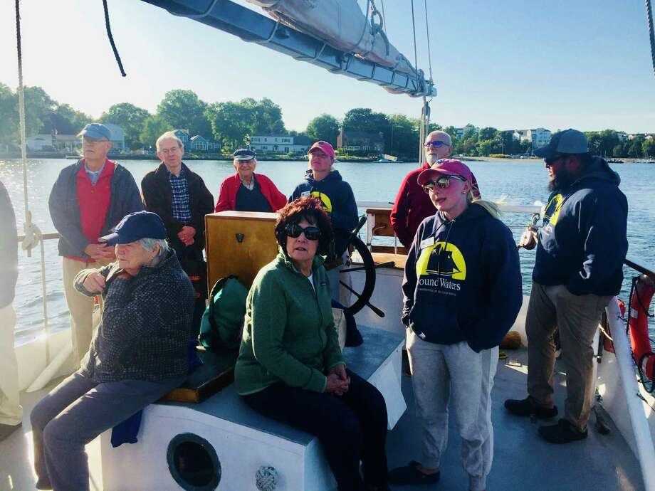 Darien Men's Association cruise on the sloop Soundwater, out of Stamford. Foreground, seated: Barbara Thorn, Arlene Tulacro. Back row: Mark Thorne, Scott Hutchinson, Andre Guilbert, (crew member at wheel), Jim Tulacro. Photo: Contributed Photo / / Connecticut Post