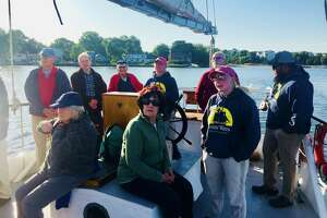 Darien Men's Association cruise on the sloop Soundwater, out of Stamford. Foreground, seated: Barbara Thorn, Arlene Tulacro. Back row: Mark Thorne, Scott Hutchinson, Andre Guilbert, (crew member at wheel), Jim Tulacro.