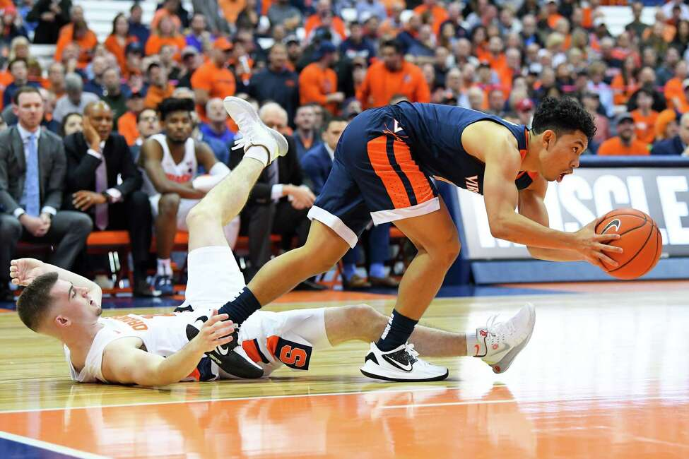 SYRACUSE, NY - NOVEMBER 06: Kihei Clark #0 of the Virginia Cavaliers gets tangled up with Joe Girard III #11 of the Syracuse Orange while controlling the ball during the second half at the Carrier Dome on November 6, 2019 in Syracuse, New York. Virginia defeated Syracuse 48-34.