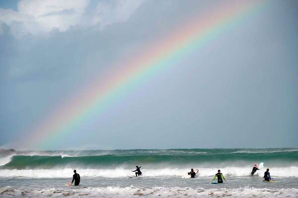 A rainbow is seen over surfers and bodyboarders at Towan Beach in Newquay, southwest England.