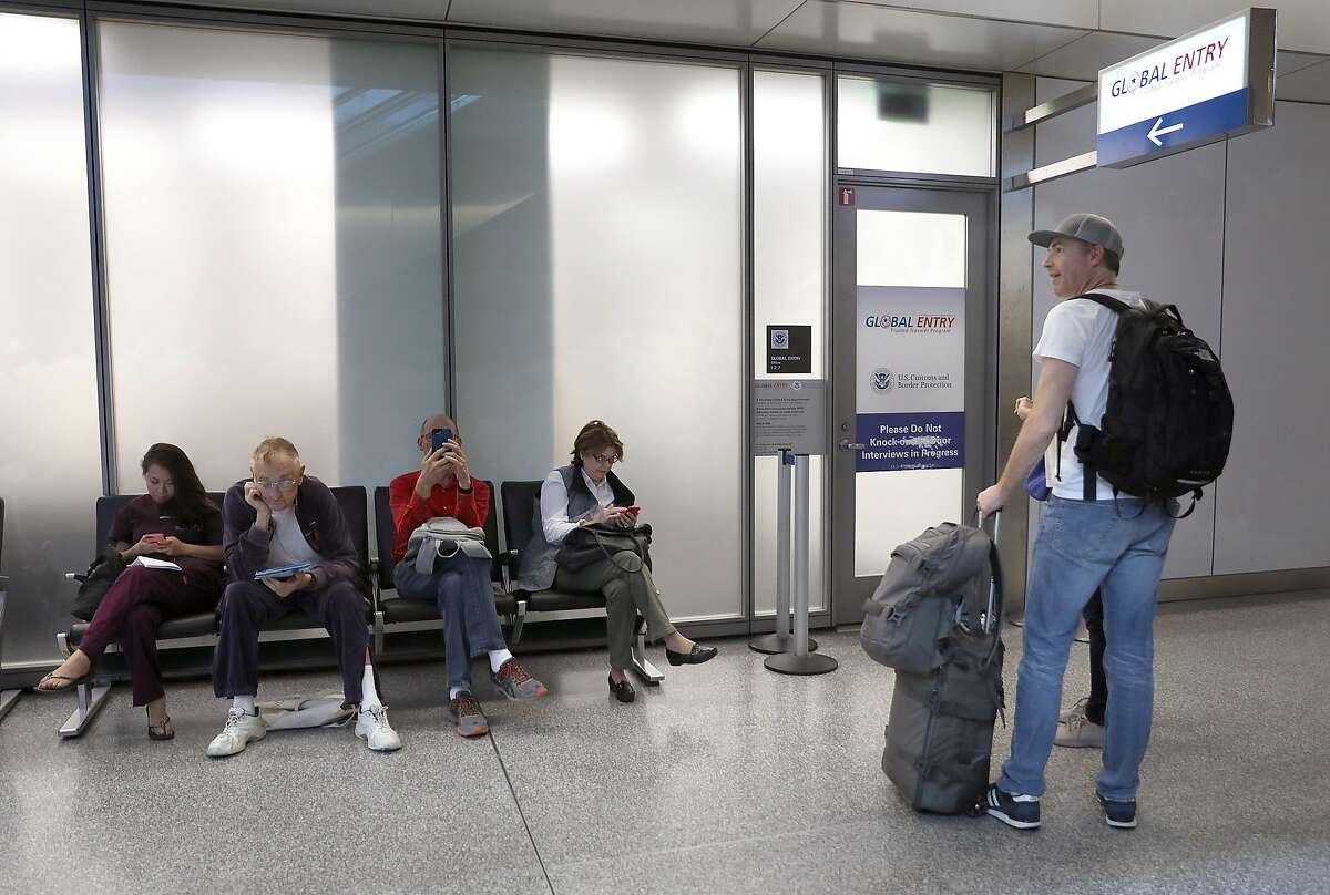 As a line of people (left) wait for their Global Entry interview appointments Eric Juban (right) from San Francisco tries to find out how to schedule an appointment at San Francisco International airport on Thursday, July 26, 2018 in San Francisco, Calif.