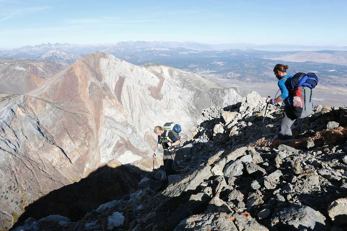 Daniel Ristow (left) and Jordan Kilgore hike near the summit of Mount Morrison to execute a wingsuit base jump on Friday, Oct. 11, 2019 near Convict Lake. Laurel Mountain is visible in the background.