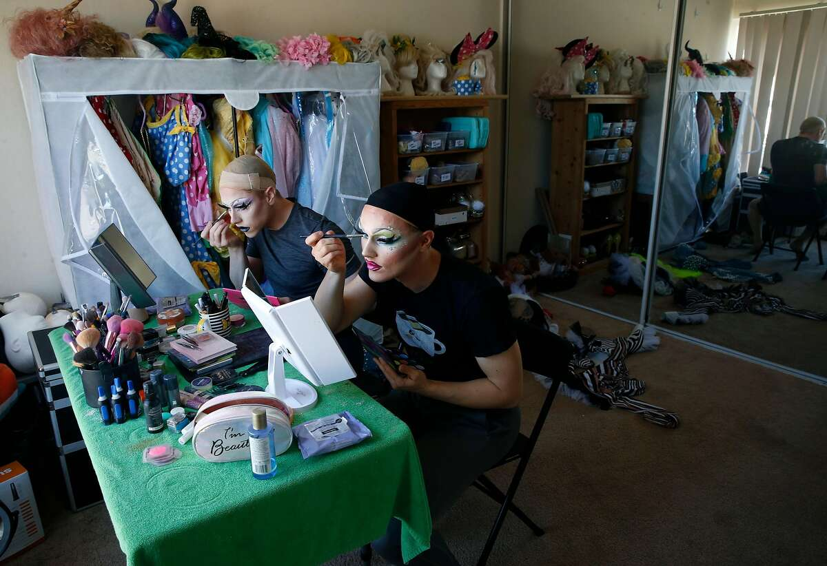 """Zachary Artice (left) and his husband Scott apply makeup before recording their popular """"Minnie and Tink"""" drag queen webcast created on the TikTok social media app in Daly City, Calif. on Saturday, Nov. 2, 2019."""