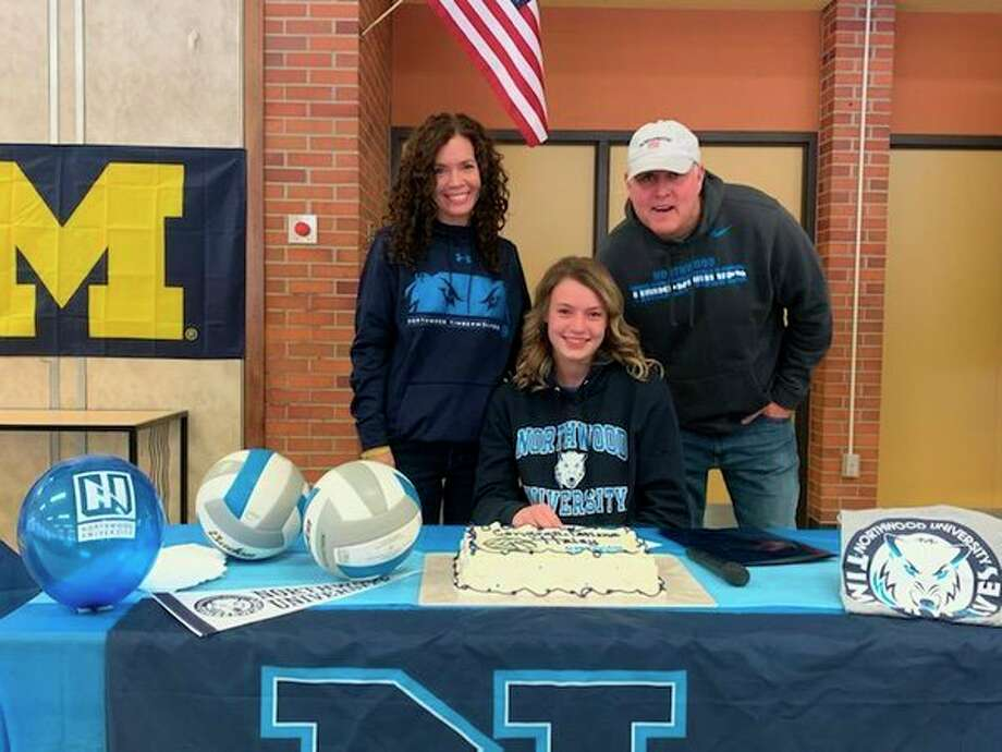 Dow High'sHaley Jaster is joined by her parents after signing with the Northwood University volleyball program.