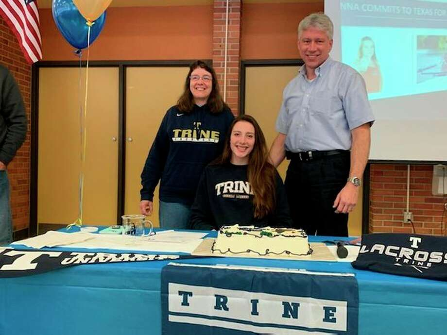 Dow High's Alyssa Keptner is joined by her parents after signing with the Trine University women's lacrosse program on Wednesday.