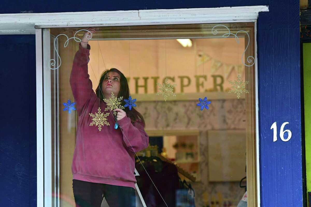 Whisper Boutique store owner Nathalie Leland decorates her Ridge St. store front window for the holidays on Thursday, Nov. 14, 2019 in Glens Falls, N.Y. (Lori Van Buren/Times Union)