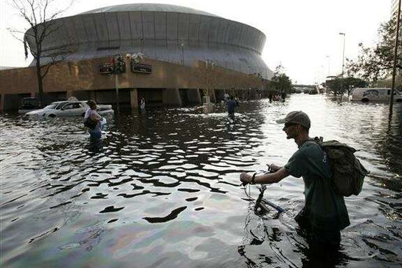 A man pushes his bicycle through flood waters near the Superdome in New Orleans after Hurricane Katrina left much of the city underwater.