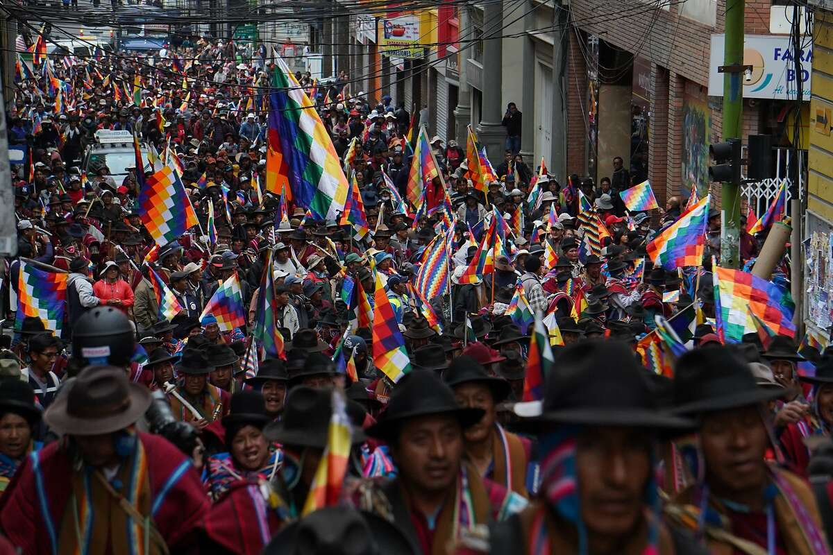 LA PAZ, BOLIVIA - NOVEMBER 14: People from el Alto wearing the traditional red ponchos wave Whipala flags and shout slogans asking the resignation of Interim President of Bolivia Jeanine ��ez during a protest on November 14, 2019 in La Paz, Bolivia. Since Evo Morales resignation due to back withdrawal from armed forces, his supporters have been flooding into the streets of El Alto clashing with police. Opposition senator Jeanine Anez self-proclaimed as new Bolivian president and presented her ministers. From the exile in Mexico, Morales said yesterday that he is ready to return to pacify Bolivia, not as a candidate. (Photo by Javier Mamani/Getty Images)