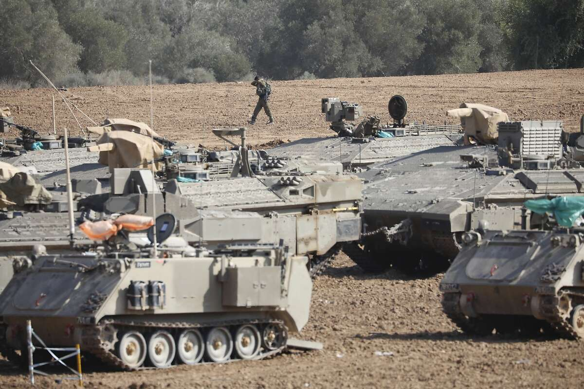 An Israeli soldier walks past military vehicles in a gathering point near the Israel-Gaza Border, Thursday, Nov. 14, 2019. Israel and the militant Islamic Jihad group in Gaza reached a cease-fire on Thursday to end the heaviest Gaza fighting in months.