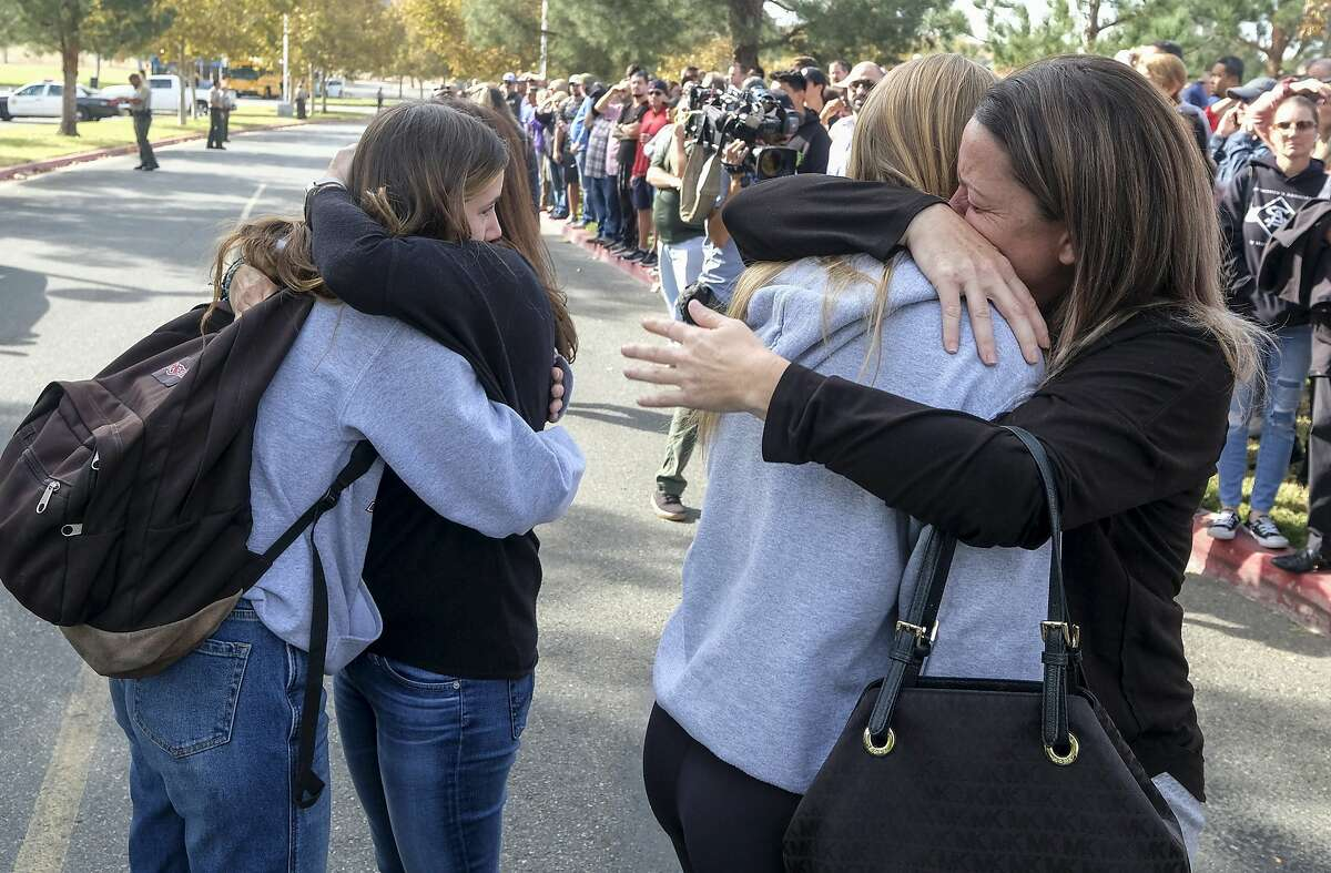 Students are embraced as they reunite at a park following a shooting at Saugus High School that injured several people, Thursday, Nov. 14, 2019, in Santa Clarita, Calif. (AP Photo/Ringo H.W. Chiu)