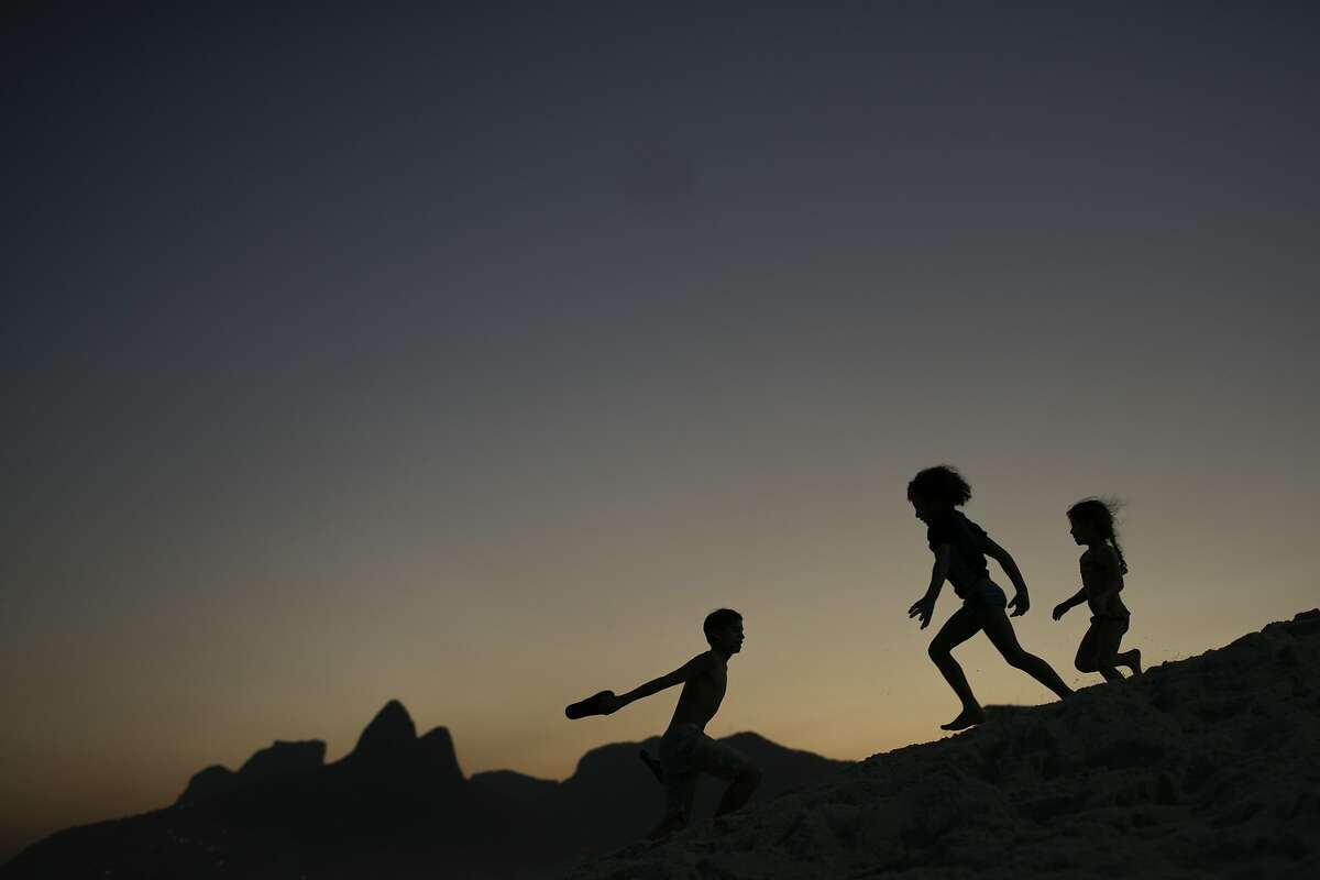 FILE - In this Aug. 1, 2016 file photo, children are silhouetted against the setting sun as they run on the sand at Ipanema beach in Rio de Janeiro, Brazil. Homeland Security investigators who uncover child exploitation initiated more than 4,000 cases around the world in 2019. Data obtained by The Associated Press shows the investigations resulted in thousands of arrests and the identification of more than 1,000 victims. On Thursday, Nov. 14, 2019, officials plan to unveil a new center based at Immigration and Customs Enforcement's headquarters in Washington tasked with alerting other countries when U.S. sex offenders are traveling there.