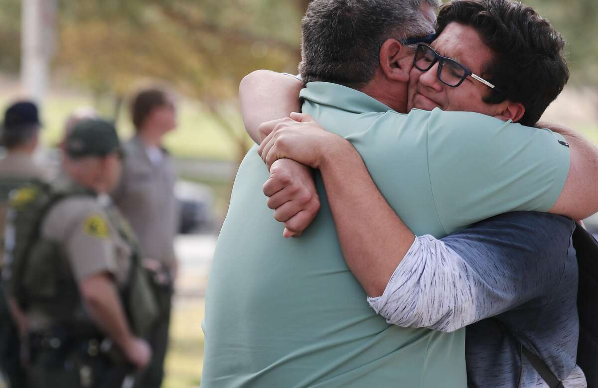 SANTA CLARITA, CALIFORNIA - NOVEMBER 14: Kurt Rennels hugs his son Eric (R) after reuniting at a park near Saugus High School after a shooting at the school left two students dead and three wounded on November 14, 2019 in Santa Clarita, California. A suspect in the shooting is being treated at a local hospital for a gunshot wound to the head.